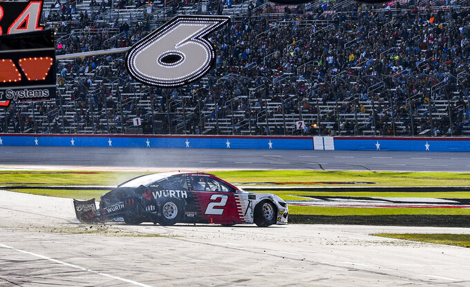 Brad Keselowski (2) wrecks into the front stretch grass during a NASCAR Cup Series auto race at Texas Motor Speedway, Sunday, Nov. 3, 2019, in Fort Worth, Texas. (AP Photo/Randy Holt)