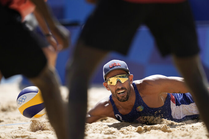 Nicholas Lucena, of the United States, dives for the ball during a men's beach volleyball match against Qatar at the 2020 Summer Olympics, Sunday, Aug. 1, 2021, in Tokyo, Japan. (AP Photo/Felipe Dana)