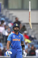 India's captain Virat Kohli throws his bat in frustration after being dismissed by New Zealand's Trent Boult during the Cricket World Cup semi-final match between India and New Zealand at Old Trafford in Manchester, England, Wednesday, July 10, 2019. (AP Photo/Aijaz Rahi)