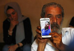Lebanese Khaldoun Mohammed, 58, shows a portrait of his son Mohammed, 27, who is still missing at sea while he was trying with other migrants to reach Cyprus on a boat, as he sits at his house in Tripoli, north Lebanon Thursday, Sept. 17, 2020. Mohammed is one of scores of people who have tried in recent weeks to flee Lebanon that is passing through its worst economic and financial crisis in decades to European Union member Cyprus. (AP Photo/Hussein Malla)