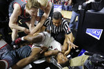 Montana's Sayeed Pridgett (4) and Eastern Washington's Kim Aiken Jr. lie entangled after a hard drive to the basket during an NCAA college basketball game in the championship of the Big Sky Tournament in Boise, Idaho, Saturday, March 16, 2019. Montana won 68-62. (AP Photo/Otto Kitsinger)