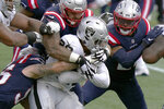New England Patriots defenders combine to tackle Las Vegas Raiders running back Josh Jacobs (28) in the first half of an NFL football game, Sunday, Sept. 27, 2020, in Foxborough, Mass. (AP Photo/Steven Senne)
