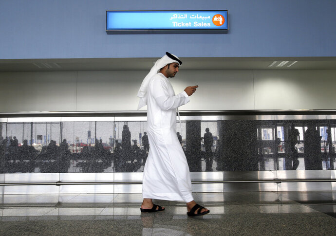 FILE - In this Oct. 27, 2013 file photo, a worker looks at his mobile phone at the newly opened Al Maktoum International Airport in Dubai, United Arab Emirates. According to a New York Times report, ToTok, a chat app that quickly became popular in the United Arab Emirates for communicating with friends and family, is actually a spying tool used by the government to track its users. (Patrick Castillo/Emarat Al Youm via AP, File)