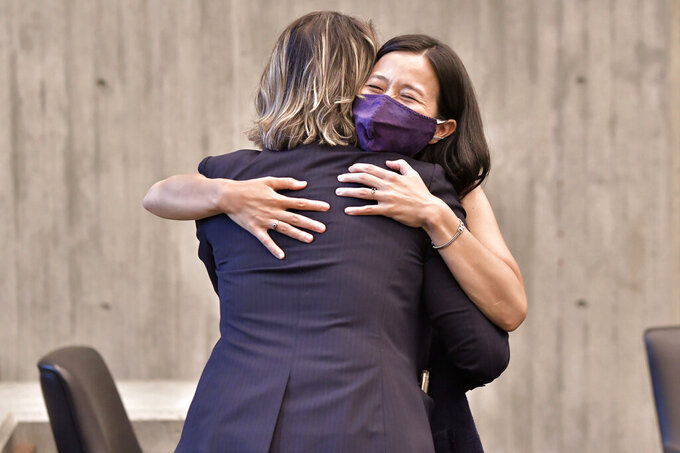 Boston mayoral candidates City Councilors, from left, Annissa Essaibi George, and Michelle Wu embrace during a city council meeting at City Hall in Boston, Wednesday, Sept. 15, 2021. Wu placed first and Essaibi George placed second in a preliminary mayoral runoff election that selected two top contenders from a field of five candidates all of whom are people of color, four of them women. (AP Photo/Josh Reynolds)