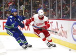Vancouver Canucks' Christopher Tanev (8) vies for the puck with Detroit Red Wings' Taro Hirose (67) during the second period of an NHL hockey game Tuesday, Oct. 15, 2019, in Vancouver, British Columbia. (Ben Nelms/The Canadian Press via AP)