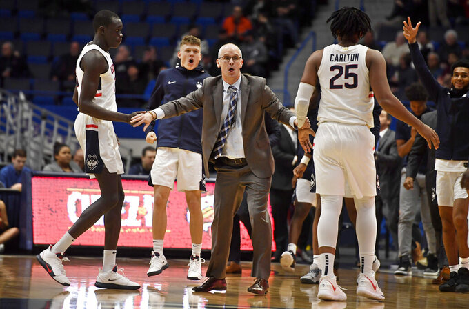 Connecticut head coach Dan Hurley, center, reacts as his players run to him during a timeout the first half of an NCAA college basketball game against Maine, Sunday, Dec. 1, 2019, in Hartford, Conn. (AP Photo/Jessica Hill)