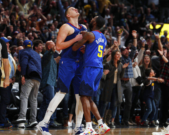 Denver Nuggets center Nikola Jokic, left, is congratulated by guard Will Barton III after hitting the winning basket in the second half of an NBA basketball game against the Philadelphia 76ers, Friday, Nov. 8, 2019, in Denver. (AP Photo/David Zalubowski)
