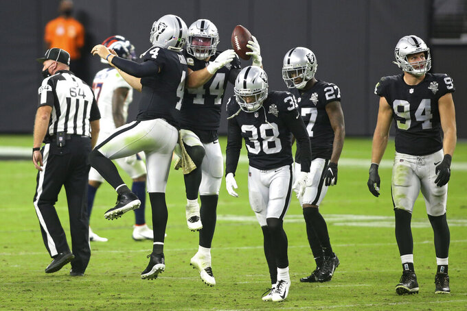 Las Vegas Raiders quarterback Derek Carr (4) celebrates with inside linebacker Nick Kwiatkoski (44) after defeating the Denver Broncos in an NFL football game, Sunday, Nov. 15, 2020, in Las Vegas. (AP Photo/Isaac Brekken)