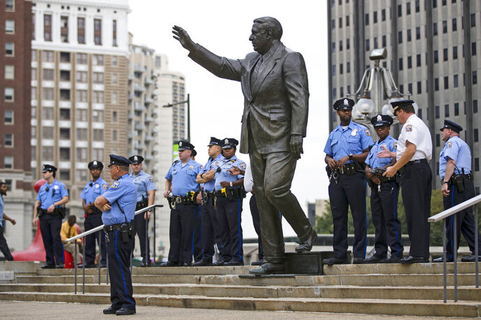 FILE – In this Sept. 14, 2017, file photo, police officers guard a statue of former Philadelphia mayor and police commissioner Frank Rizzo on Thomas Paine Plaza outside the Municipal Services Building in Philadelphia. Mayor Jim Kenney told philly.com on Thursday, Aug. 9, 2018 the planned relocation of the Rizzo statue is being put on hold for at least two more years. (AP Photo/Matt Rourke, File)
