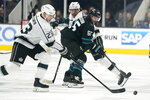 Los Angeles Kings left wing Dustin Brown (23) skates past San Jose Sharks defenseman Erik Karlsson (65) during the second period of an NHL hockey game in San Jose, Calif., Friday, Nov. 29, 2019. (AP Photo/Tony Avelar)