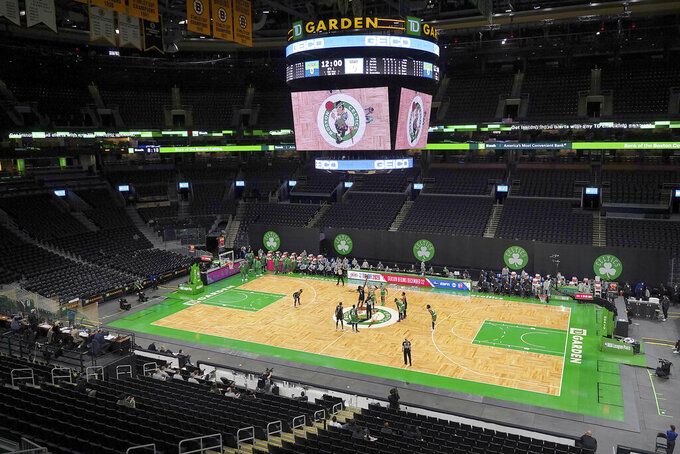 FILE - In this Dec. 18, 2020, file photo, the Boston Celtics and Brooklyn Nets tip off in front of empty seats at TD Garden to start an NBA preseason basketball game in Boston during the COVID-19 pandemic. The Celtics and the NHL Boston Bruins will be able to start playing in front of a limited number of fans beginning March 22, 2021, under Phase 4 of Massachusetts' reopening plan. (AP Photo/Mary Schwalm, File)