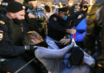 Police officers detain a protester during a rally to cancel the results of voting on amendments to the Constitution in Pushkin Square in Moscow, Russia, Wednesday, July 15, 2020. Earlier this month a group of opposition activists called for a protest against the constitutional reform that allows Russian President Vladimir Putin to stay in power until 2036. (AP Photo/Alexander Zemlianichenko)