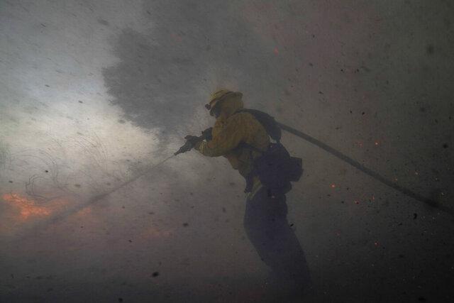 A firefighter battles the Silverado Fire Monday, Oct. 26, 2020, in Irvine, Calif. (AP Photo/Jae C. Hong)