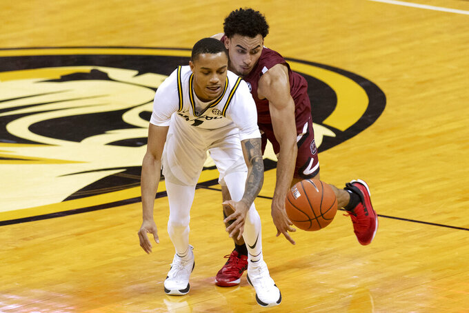 Missouri's Xavier Pinson, left, has the ball knocked away by South Carolina's Justin Minaya during the second half of an NCAA college basketball game Tuesday, Jan. 19, 2021, in Columbia, Mo. (AP Photo/L.G. Patterson)