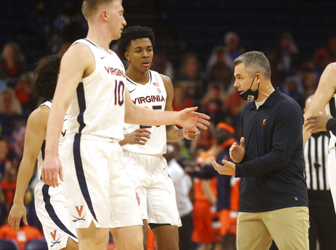 Virginia head coach Tony Bennett, right, talks with his players during an NCAA college basketball game against Syracuse, Monday, Jan. 25, 2021, in Charlottesville, Va. (Andrew Shurtleff/The Daily Progress via AP)