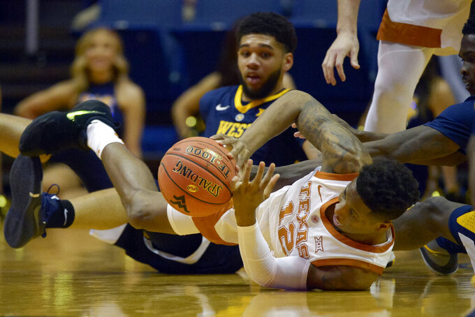 Texas guard Kerwin Roach II (12) tries to pass after falling as West Virginia forwards Wesley Harris and Esa Ahmad try to grab the ball during the first half of an NCAA college basketball game in Morgantown, W.Va., Saturday, Feb. 9, 2019. (AP Photo/Craig Hudson)