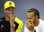 Mercedes driver Lewis Hamilton of Britain laughs with Renault driver Daniel Ricciardo of Australia during a news conference at the Silverstone racetrack, in Silverstone, England, Thursday, July 11, 2019. The British Formula One Grand Prix will be held on Sunday. (AP Photo/Luca Bruno)