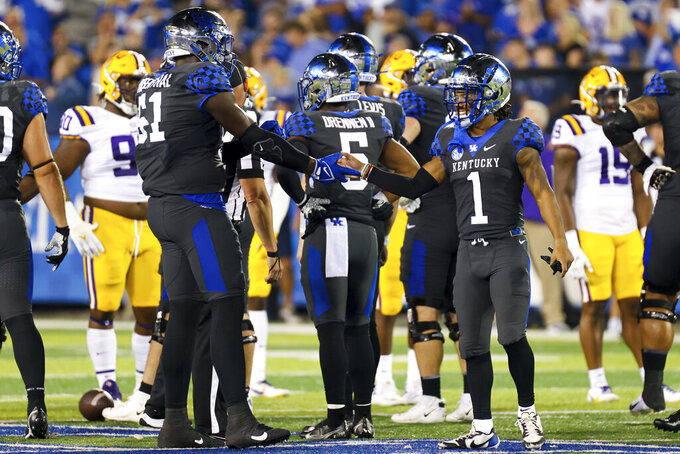Kentucky wide receiver Wan'Dale Robinson (1) slaps hands with offensive lineman Dare Rosenthal (51) after the team's win in an NCAA college football game against LSU in Lexington, Ky., Saturday, Oct. 9, 2021. (AP Photo/Michael Clubb)