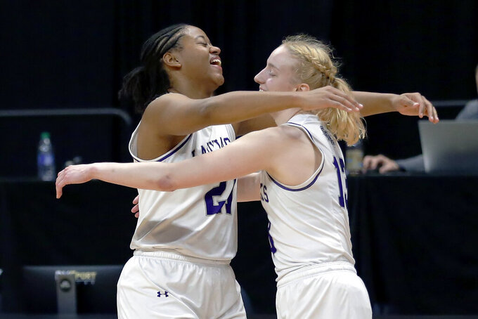 Stephen F. Austin forward Aiyana Johnson (21) and guard Stephanie Visscher (13) hug as the buzzer sounds on their win against Sam Houston State after an NCAA college basketball game for the Southland Conference women's tournament championship Sunday, March 14, 2021, in Katy, Texas. (AP Photo/Michael Wyke)