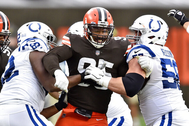 FILE - Cleveland Browns defensive end Myles Garrett (95) rushes the passer during the first half of an NFL football game against the Indianapolis Colts in Cleveland, in this Sunday, Oct. 11, 2020, file photo. Browns defensive star Myles Garrett was activated from the COVID-19 list after missing two games, clearing the end and sack specialist to return this week against Tennessee. (AP Photo/David Richard, File)