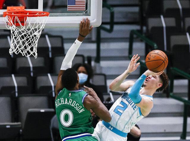 Charlotte Hornets guard LaMelo Ball (2) attempts a shot as Dallas Mavericks guard Josh Richardson (0) defends during the first half of an NBA basketball game, Wednesday, Dec. 30, 2020, in Dallas. Charlotte won 118-99. (AP Photo/Brandon Wade)