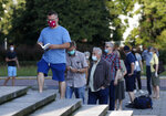 People, keeping social distancing, wait in line to cast their vote in presidential election in Warsaw, Poland, Sunday, June 28, 2020. The election will test the popularity of incumbent President Andrzej Duda who is seeking a second term and of the conservative ruling party that backs him. (AP Photo/Petr David Josek)