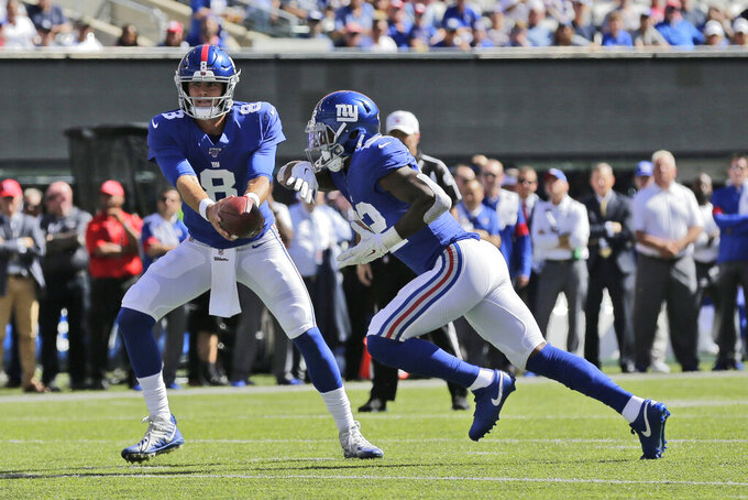 New York Giants quarterback Daniel Jones, left, hands off to Wayne Gallman during the first half of an NFL football game against the Washington Redskins, Sunday, Sept. 29, 2019, in East Rutherford, N.J. (AP Photo/Adam Hunger)