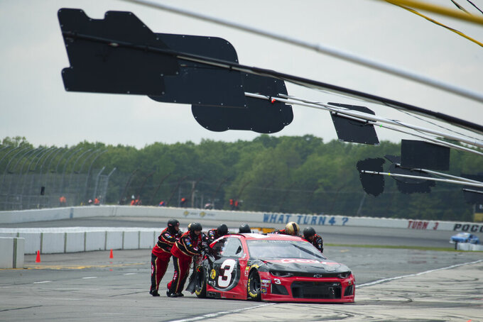 Crew members push the wrecked car of Austin Dillon to the garage area during a NASCAR Cup Series auto race at Pocono Raceway, Sunday, June 2, 2019, in Long Pond, Pa. (AP Photo/Matt Slocum)