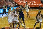 West Virginia guard Miles McBride (4) drives the ball against Texas forward Brock Cunningham (30) during the first half of an NCAA college basketball game, Saturday, Feb. 20, 2021, in Austin, Texas. (AP Photo/Michael Thomas)