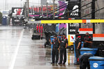 Crew members watch as rain falls before a NASCAR Cup Series auto race at Charlotte Motor Speedway Wednesday, May 27, 2020, in Concord, N.C. (AP Photo/Gerry Broome)