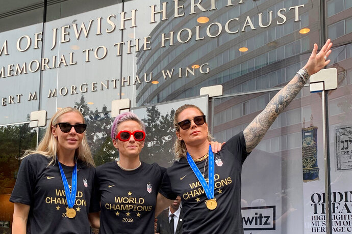 In this Wednesday, July 10, 2019 photo provided by Jeff Simmons, U.S. women's soccer player Ashlyn Harris raises her left arm next to her teammates, Allie Long and Megan Rapinoe, outside the Museum of Jewish Heritage before a victory parade in New York City, to celebrate the team's Women's World Cup title. On Friday, July 19, 2019, The Associated Press reported on stories circulating online incorrectly asserting that Harris is giving a Nazi salute. This photo was made after the museum hosted a breakfast for players before the ticker-tape parade, said Simmons, the executive vice president for Anat Gerstein, Inc., a public relations firm that works with the museum. (Jeff Simmons via AP)