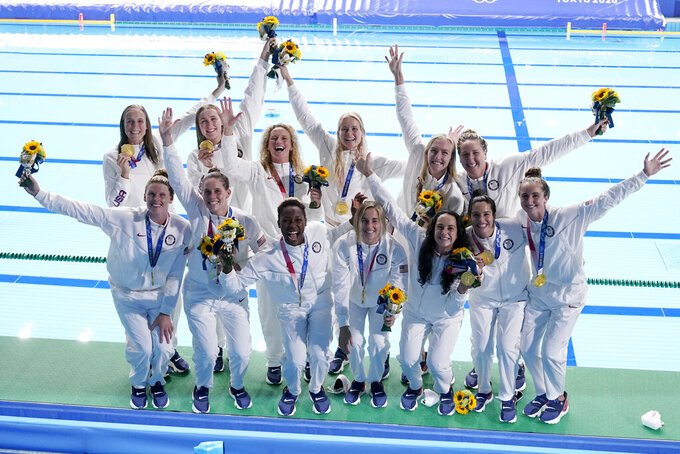 The United States women's water polo team poses with their gold medals after defeating Spain at the 2020 Summer Olympics, Saturday, Aug. 7, 2021, in Tokyo, Japan. (AP Photo/Mark Humphrey)