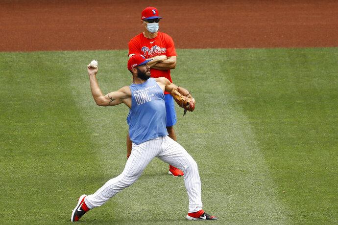 Philadelphia Phillies' Jake Arrieta, front, warms up near manager Joe Girardi during baseball practice at Citizens Bank Park, Tuesday, July 7, 2020, in Philadelphia. (AP Photo/Matt Slocum)