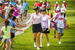 Paula Creamer of California, left, and her playing partner Morgan Pressel of Florida, right, high-five fans as they play in the second round of the Dow Great Lakes Bay Invitational golf tournament on Thursday, July 18, 2019 at Midland Country Club in Midland, Mich. (Katy Kildee/Midland Daily News via AP)