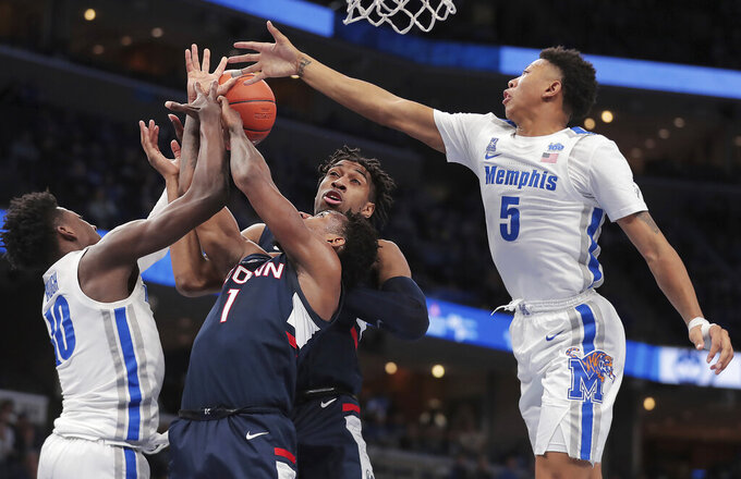 Memphis guards Damion Baugh, left,and Boogie Ellis (5) battle for a rebound with the Connecticut's Christian Vital (1) and Isaiah Whaley during an NCAA college basketball game, Saturday, Feb. 1 2020, at the FedExForum in Memphis, Tenn. (Jim Weber/Daily Memphian via AP)