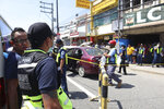 In this Oct. 18, 2019 handout photo provided by the Olongapo Public Information Office, police check on an Australian named Anthony George inside a car in Olongapo, northern Philippines. Philippine police city director of Olongapo city said they arrested Australian Michael McLaren shortly after the incident for the alleged killing of George and Filipino Mila Bailey inside the car. Another Australian victim, Wayne Bailey, is still recovering at the hospital from gunshot wounds. (Olongapo Public Information Office via AP)