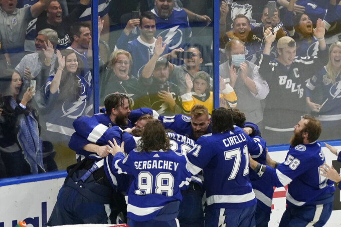 Tampa Bay Lightning teammates surround goaltender Andrei Vasilevskiy after the Lighting defeated the Montreal Canadiens 1-0 to win the Stanley Cup in Game 5 of the NHL hockey finals, Wednesday, July 7, 2021, in Tampa, Fla. (AP Photo/Gerry Broome)