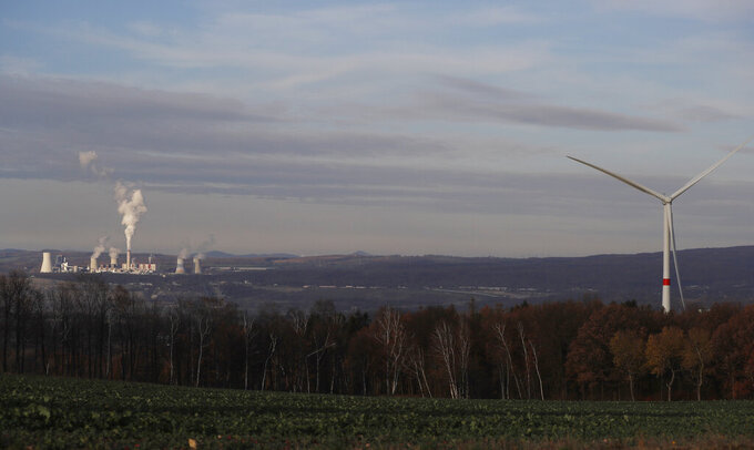 FILE - In this Tuesday, Nov. 19, 2019 file photo, smoke rises from chimneys of the Turow power plant located by the Turow lignite coal mine near the town of Bogatynia, Poland. European Union's top court has on Friday, May 21, 2021 ordered Poland to immediately stop extracting brown coal at the Turow mine on the border with the Czech Republic and Germany. The Czech Republic filed in March for an injunction, saying the mine drains away water from its inhabited areas. (AP Photo/Petr David Josek, file)
