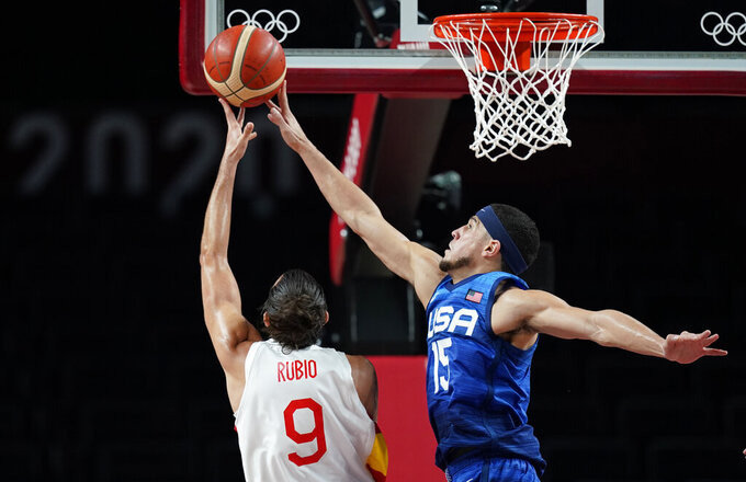United States' Devin Booker (15), right, tries to block a shot by Spain's Ricky Rubio (9) during men's basketball quarterfinal game at the 2020 Summer Olympics, Tuesday, Aug. 3, 2021, in Saitama, Japan. (AP Photo/Charlie Neibergall)
