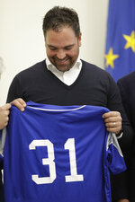 Hall of Fame catcher Mike Piazza shows his jersey during his presentation as Italy's national baseball team coach, at the Italian Olympic Committee headquarters in Rome, Friday, Nov. 29, 2019.  (AP Photo/Alberto Pellaschiar)