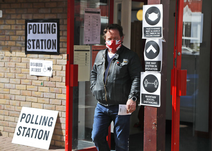 A man wearing a face mask leaves the polling station at St Albans Church after voting, in London, Thursday, May 6, 2021. Millions of people across Britain will cast a ballot on Thursday, in local elections, the biggest set of votes since the 2019 general election. A Westminster special-election is also taking place in Hartlepool, England.(AP Photo/Frank Augstein)