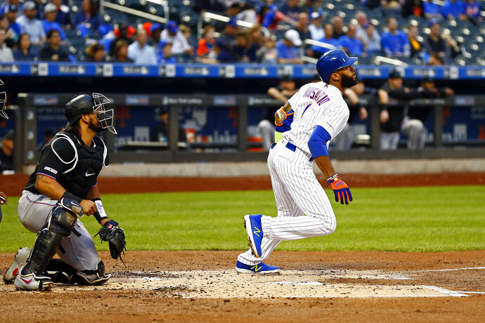 New York Mets' Amed Rosario watches his grand slam in front of Miami Marlins catcher Jorge Alfaro during the first inning of a baseball game Friday, May 10, 2019, in New York. (AP Photo/Adam Hunger)