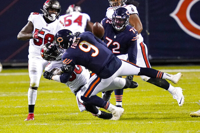 Chicago Bears quarterback Nick Foles (9) fumbles the ball as he's sacked by Tampa Bay Buccaneers outside linebacker Jason Pierre-Paul (90) during the second half of an NFL football game in Chicago, Thursday, Oct. 8, 2020. The Bears recovered the fumble, (AP Photo/Charles Rex Arbogast)