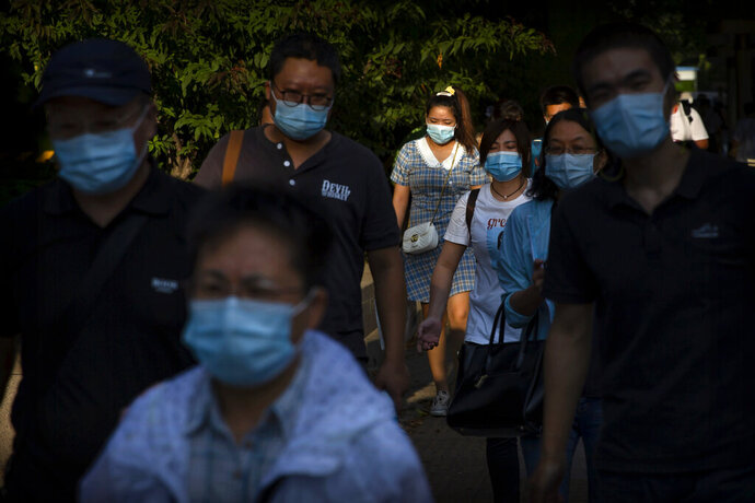 People wearing face masks to protect against the coronavirus walk along a street in the central business district in Beijing, Wednesday, Sept. 2, 2020. Even as China has largely controlled the outbreak, the coronavirus is still surging across parts of the world. (AP Photo/Mark Schiefelbein)