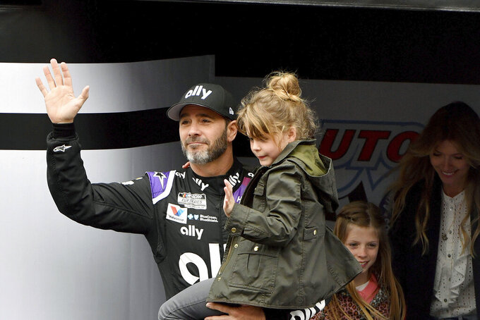 FILE - In this March 1, 2020, file photo, Jimmie Johnson is introduced to the crowd during activities as he carries his youngest daughter Lydia as his oldest daughter Genevieve and wife Chandra follow prior to a NASCAR Cup Series auto race in Fontana, Calif. Jimmie Johnson wanted to retire from full-time racing to step away from NASCAR's 11-month grind. The coronavirus pandemic has brought his final season to an unexpected pause, and now the seven-time champion isn't sure what his future holds. (AP Photo/Will Lester, File)