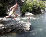 A man jumps into the Treska River, just west of Skopje, North Macedonia, Wednesday July 28, 2021. Authorities in North Macedonia have issued a weather warning and recommended a set of measures on Wednesday as the tiny Balkan country is facing extreme high temperatures rising over 43 Celsius degrees (109 Fahrenheit). (AP Photo/Boris Grdanoski)