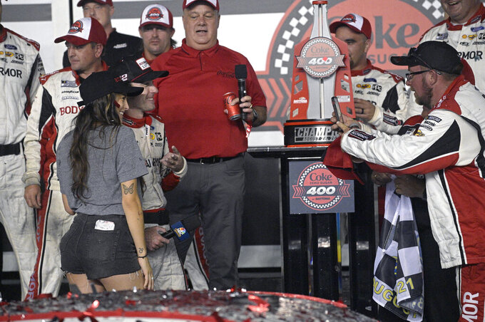 Ryan Blaney poses with his girlfriend Gianna Tulio, front, in Victory Lane after winning a NASCAR Cup Series auto race at Daytona International Speedway, Saturday, Aug. 28, 2021, in Daytona Beach, Fla. (AP Photo/Phelan M. Ebenhack)
