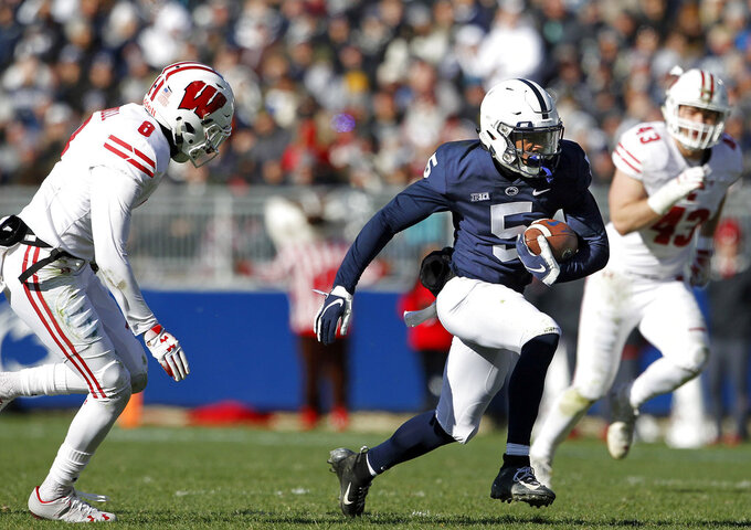 Penn State's Jahan Dotson (5) takes off running after a catch as Wisconsin's Deron Harrell (8) gives chase during the first half of an NCAA college football game in State College, Pa., Saturday, Nov. 10, 2018. (AP Photo/Chris Knight)
