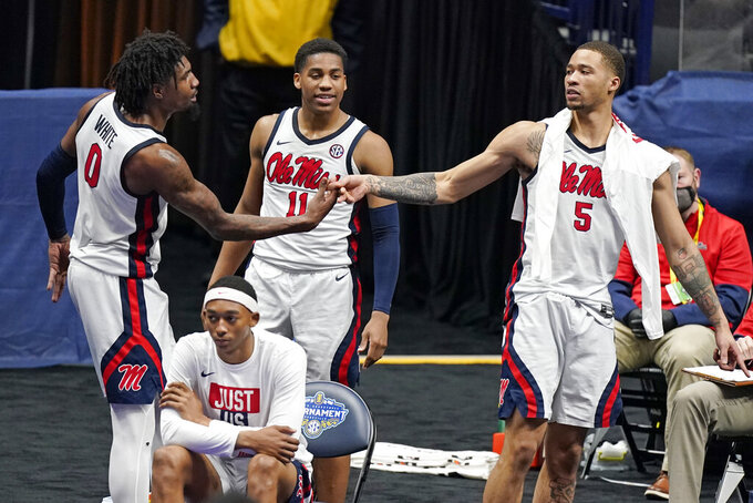 Mississippi's Romello White (0), KJ Buffen (5) and Matthew Murrell (11) celebrate in the final seconds of a win over South Carolina in an NCAA college basketball game in the Southeastern Conference Tournament Thursday, March 11, 2021, in Nashville, Tenn. (AP Photo/Mark Humphrey)