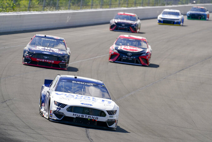 Chris Buescher (17) drives into turn one ahead of a group during a NASCAR Cup Series auto race at Pocono Raceway, Sunday, June 27, 2021, in Long Pond, Pa. (AP Photo/Matt Slocum)